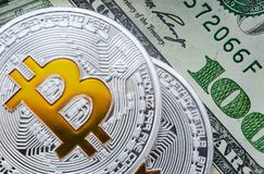 A symbolic coins of bitcoin on banknotes of one hundred dollars. Close up shot of a symbolic coins of bitcoin on banknotes of one hundred dollars. Exchange royalty free stock images