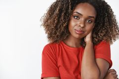 Close-up shot of tender and gentle romantic african-american girlfriend in red casual t-shirt touching back of neck shy. And cute tilting head, smiling royalty free stock photos