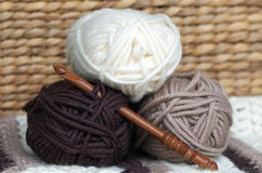 Wool balls. Close up shot of three wool balls of complementary winter or autumn colours (cream, taupe and brown) with pretty wood crochet hook Stock Image
