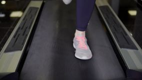 Close up shot of the treadmill on which the girl is actively running. Close up shot of the tread, which is located in the health club, which quickly passes by a stock video