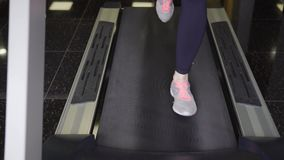 Close up shot of the treadmill on which the girl is actively running. Close up shot of the tread, which is located in the health club, which quickly passes by a stock video footage
