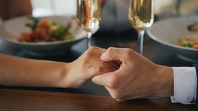 Close-up shot of two hands male and female on table with sparkling champagne glasses and plates with food. Romance. Young love and fancy restaurants concept stock footage