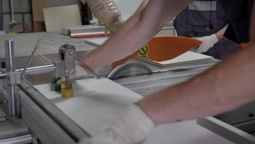 Close up shot of a two industrial workers pushing wooden board through the cutting machine. Two carpenters operating on a circular saw machine stock video footage