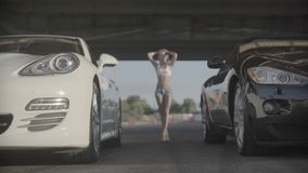 Close up shot of two new sport racing modern cars ready to start with attractive sexy young fit woman in the background. A car race on empty highway road stock footage