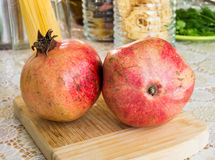 Close up shot of two red pomegranates on a wooden board Royalty Free Stock Image