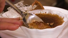 Close up of a spoon picking up some creme brule. Close up shot of two spoons breaking through the crust of a small bowl of creme brule. Spun sugar and a biscuit stock video footage