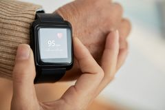 Checking Pulse with Smartwatch. Close-up shot of unrecognizable doctor checking pulse of her senior patient with help of smart watch, blurred background Stock Photo