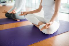 Meditating at Fitness Club. Close-up shot of unrecognizable women sitting in lotus position and meditating at modern spacious fitness club Royalty Free Stock Photography