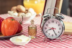 close-up shot of vintage alarm clock with various products and recipe book stock image