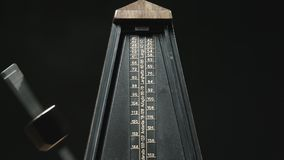 Close-up shot of vintage metronome with golden pendulum stock footage