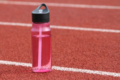 Water Bottle Track. A close up shot of a water bottle on a track outside Stock Photos