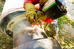 Close up shot welder until welding, sparks flying around. Welder working on a pipeline in construction site wearing overall and safety equipment Royalty Free Stock Photos