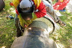 Close up shot welder until welding, sparks flying around. Welder working on a pipeline in construction site wearing overall and safety equipment Stock Images