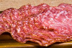 Close up shot of well folded salami on a wooden board and canvas Royalty Free Stock Photography