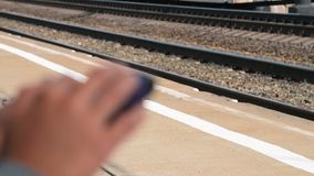 Using mobile while waiting for the train on platform. Close-up shot of a woman browsing web on mobile when waiting for the train platform. Focus on the rail stock footage