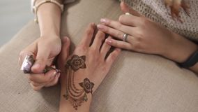 Drawing mehndi with a cone. Close up shot of a woman connecting henna flowers on a hand. Woman is using henna cone for drawings. Dying hands skin stock footage