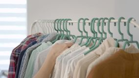Close-up shot of a woman hand going through light tonned clothes on the rack at home. Choosing stylish clothes, fashionable wardrobe stock footage