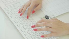 Close-up shot of woman hand typing on the computer keyboard in the modern office. At the table stock video footage
