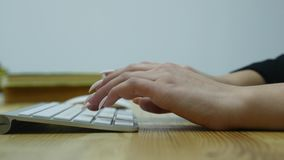 Close up shot of woman hand typing on the computer keyboard in the modern office at the table.  stock video footage