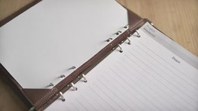 Close up shot of woman hands opening metal steel binder on leather cover note book pad daily planner organizer journal. Close up shot of elegant light brown stock video footage