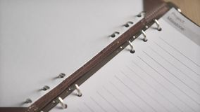 Close up shot of woman hands opening metal steel binder on leather cover organizer daily planner journal note book pad. Close up shot of elegant light brown stock video