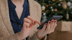 Young pretty woman using smartphone at home. Close-up shot of woman hands with smartphone at home. Christmas holiday bokeh background. Technology, winter and stock video