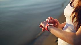 Close up shot of woman hands using smart watches on the beach near the sea. stock footage