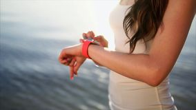 Close up shot woman hands using smart watches in front of the sea during sunset. stock video