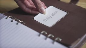 Close up shot of woman hands using sticker tag in brown leather note book pad habit tracker bullet journal planner. Close up shot of elegant business project stock footage