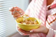 A close up shot of a woman holding a bowl of cereal Stock Image