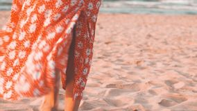 Close up shot of woman legs in red dress walking on the beach at sunset