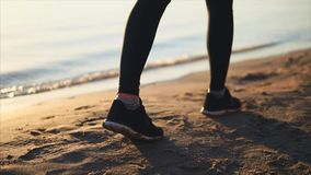 Close up shot of woman legs shod in sneakers walking on the sand beach stock footage