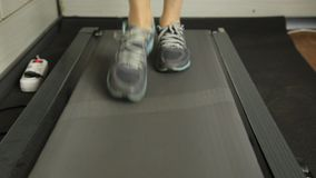 Close-up shot of Woman running on a treadmill. Sports concept stock video footage