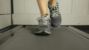 Close-up shot of Woman running on a treadmill. Sports concept stock footage