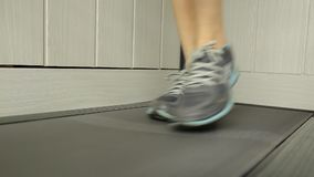 Close-up shot of Woman running on a treadmill. Sports concept.  stock footage