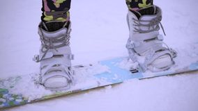 Close up shot of woman`s legs with snowboarding equipment. stock video