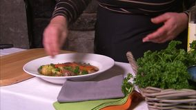 Garnishing a beef stew. A close up shot of a woman wearing black as she garnish a beef stew dish stock video