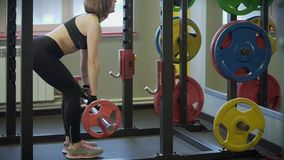 Close up shot of a woman who lifts a dumbbell with a load in a semi-crouch. stock footage