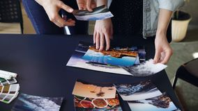 Close-up shot of women`s hands placing pictures on modern table and dividing them in groups. Color palette, markers and. Tea cup are on desk. Creative work in stock video footage