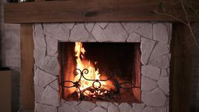 Close up shot on wood burning slowly with orange and yellow fire flame in modern stone decorated fireplace. Rural life stock video