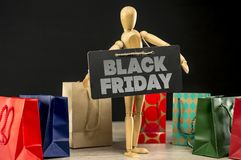 Black Friday shopping. Close up shot of a wooden mannequin holding a blackboard sign writing Black Friday and shopping bags in the background Stock Images