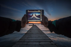 Close-up shot of working tablet on sunset and sea background Stock Image