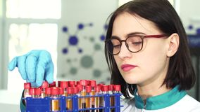 Close up of a young female researcher examining test tubes with blood samples. Close up shot of a young attractive female scientist wearing glasses examining stock video
