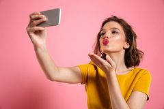 Close-up shot of young attractive woman with bright makeup sendi. Ng air kiss while taking selfie on mobile phone, isolated over pink background Stock Photos