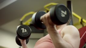Bearded athlete lifting the dumbbells and working his biceps on bench in gym, close-up stock video footage