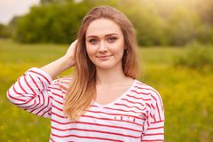 Close up shot of young beautiful Caucasian girl dressed striped casual shirt posing in meadow, looking smiling directly at camera royalty free stock photo