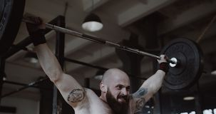 Close-up shot of young Caucasian athlete man lifting heavy weight barbell in large hardcore gym hall, extreme training. Ambition and challenge concept stock video footage