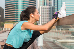 Close up shot of young fitness woman working out on the city street doing exercises, stretching her legs, standing in a Stock Photography