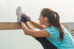 Close up shot of young fitness woman working out on the city street doing exercises, stretching her legs, standing in a Stock Photos