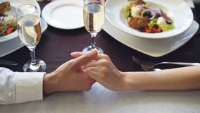 Close-up shot of young lovers touching and holding hands in classy restaurant. Table with sparkling champagne glasses. Close-up shot of young lovers touching and stock footage